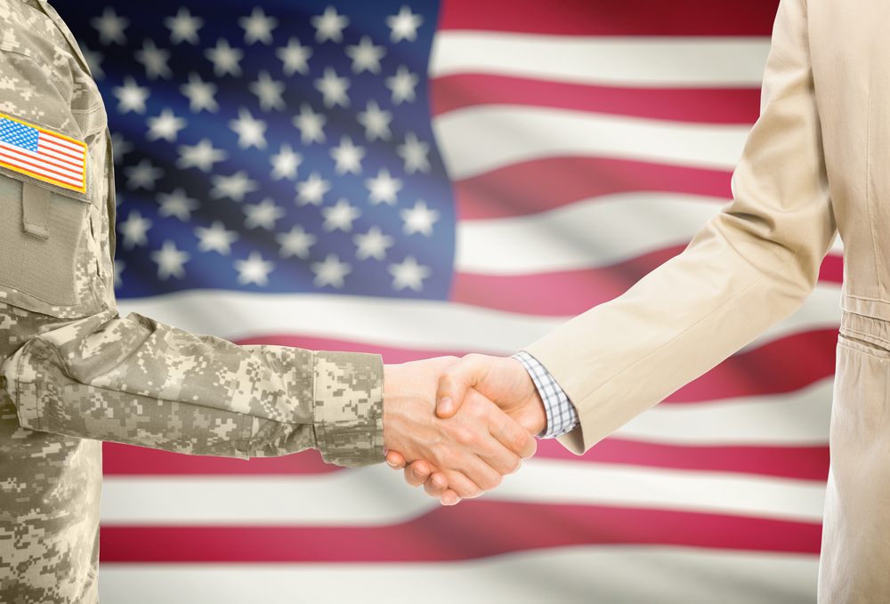 Veteran - soldier and businessman shaking hand in front of flag