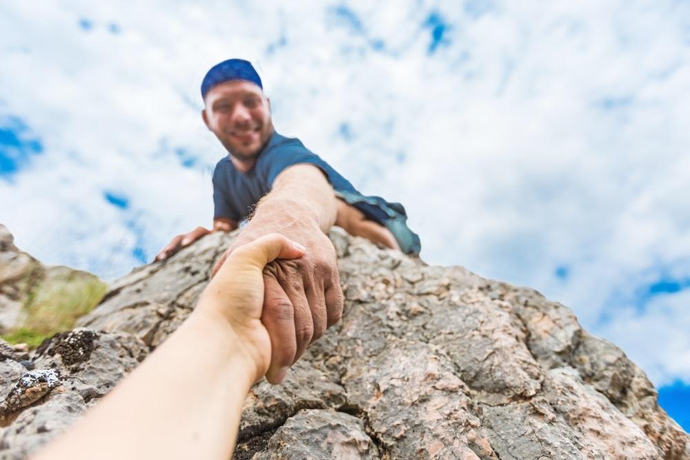 leadership - rock climber offering hand